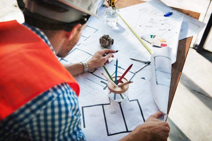 muz-v-prilbe-papiere-projekt-projektova-dokumentacia-ceruzka-kresba-dom-stavebny-dennik