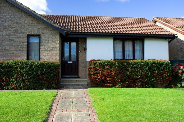 prizemny-montovany-dom-bungalov-jedno-poschodie-kriky-trava-chodnik