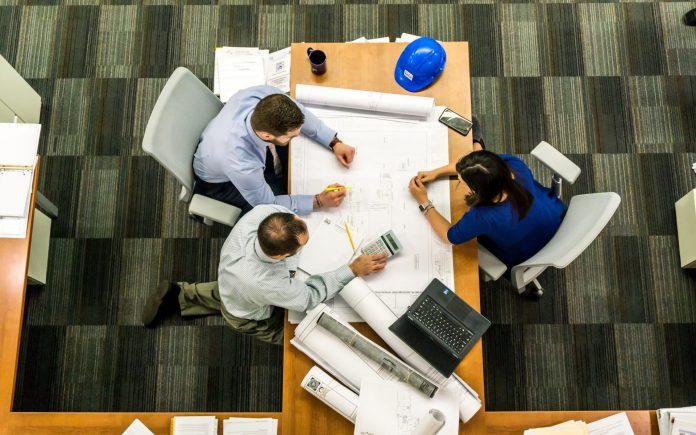 ludia-sedia-za-stolom-papiere-vykresy-projekt-notebook-kalkulacka-pocitaju-rozmery-miestnosti