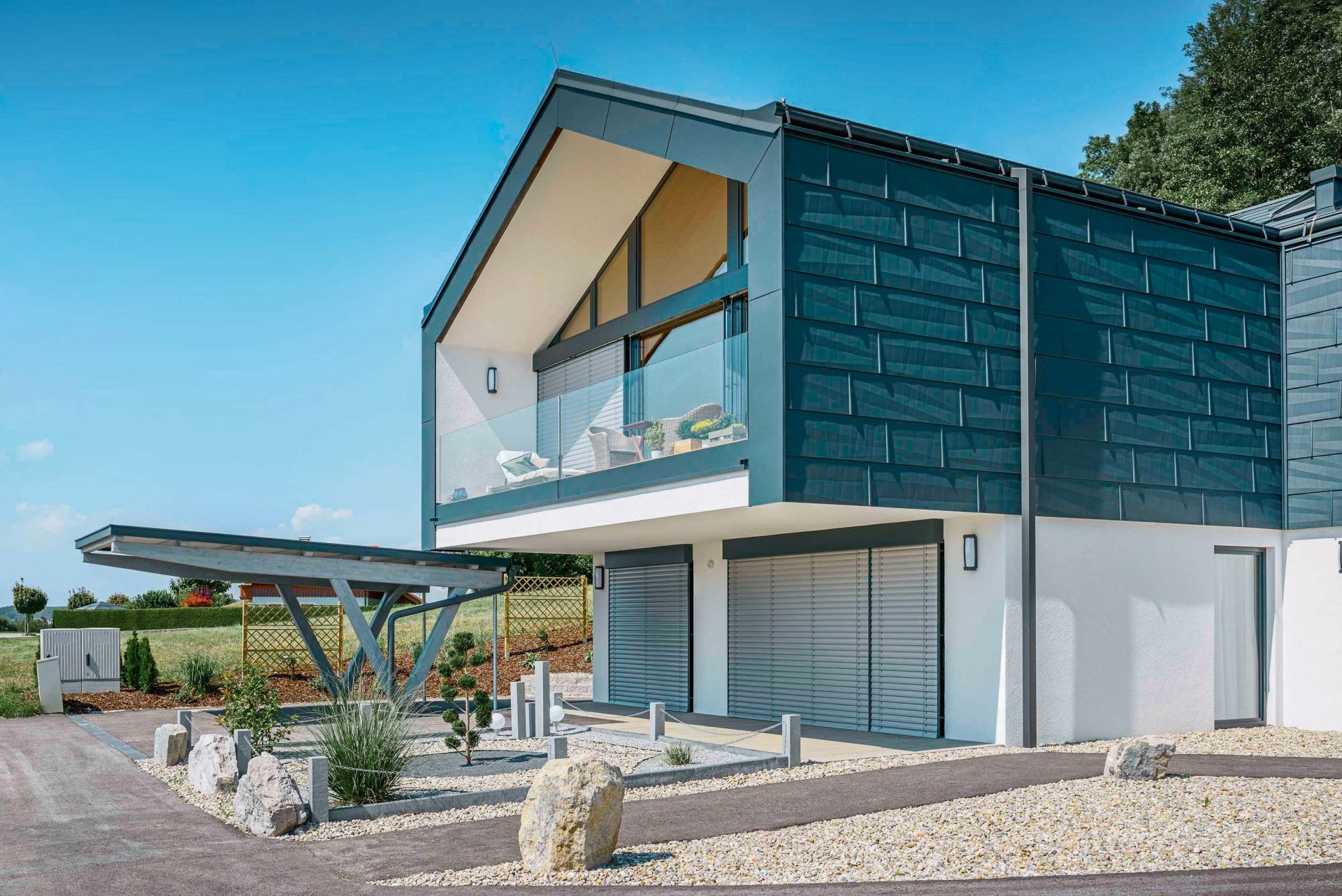 dom-stavba-novostavba-pozemok-kamene-skaly-velke-okna-strecha-terasa-dreve-brana